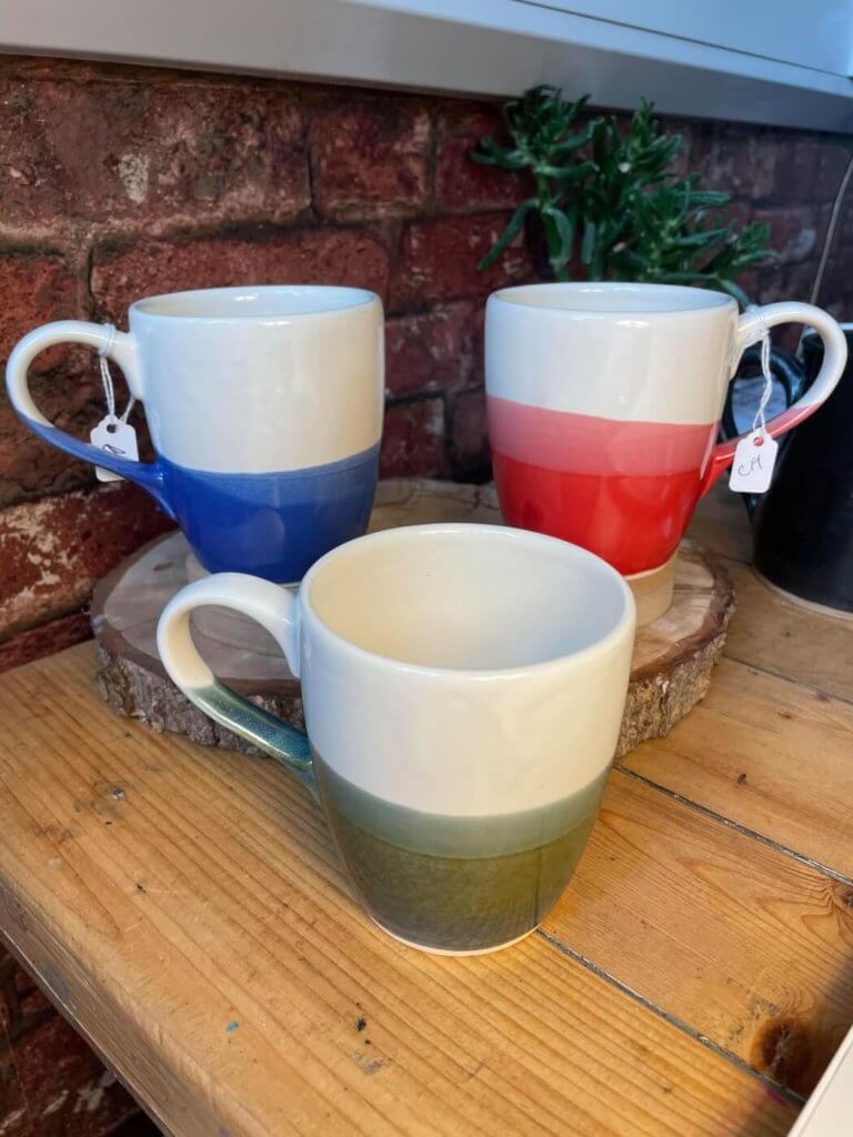 a blue and white, red and white, and green and white mug made by Ciaran Headley of CH Pottery