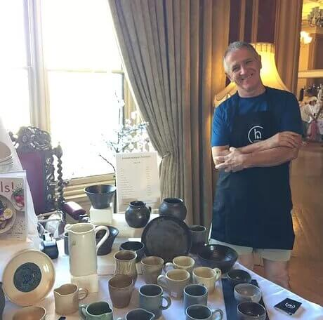 A picture of Ciaran Headley, owner of CH Pottery, standing beside a table of his ceramics.