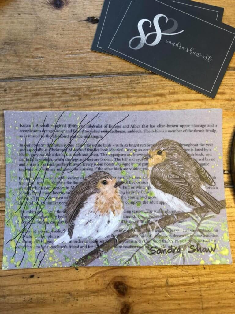 a print of two robins with a poem in the background