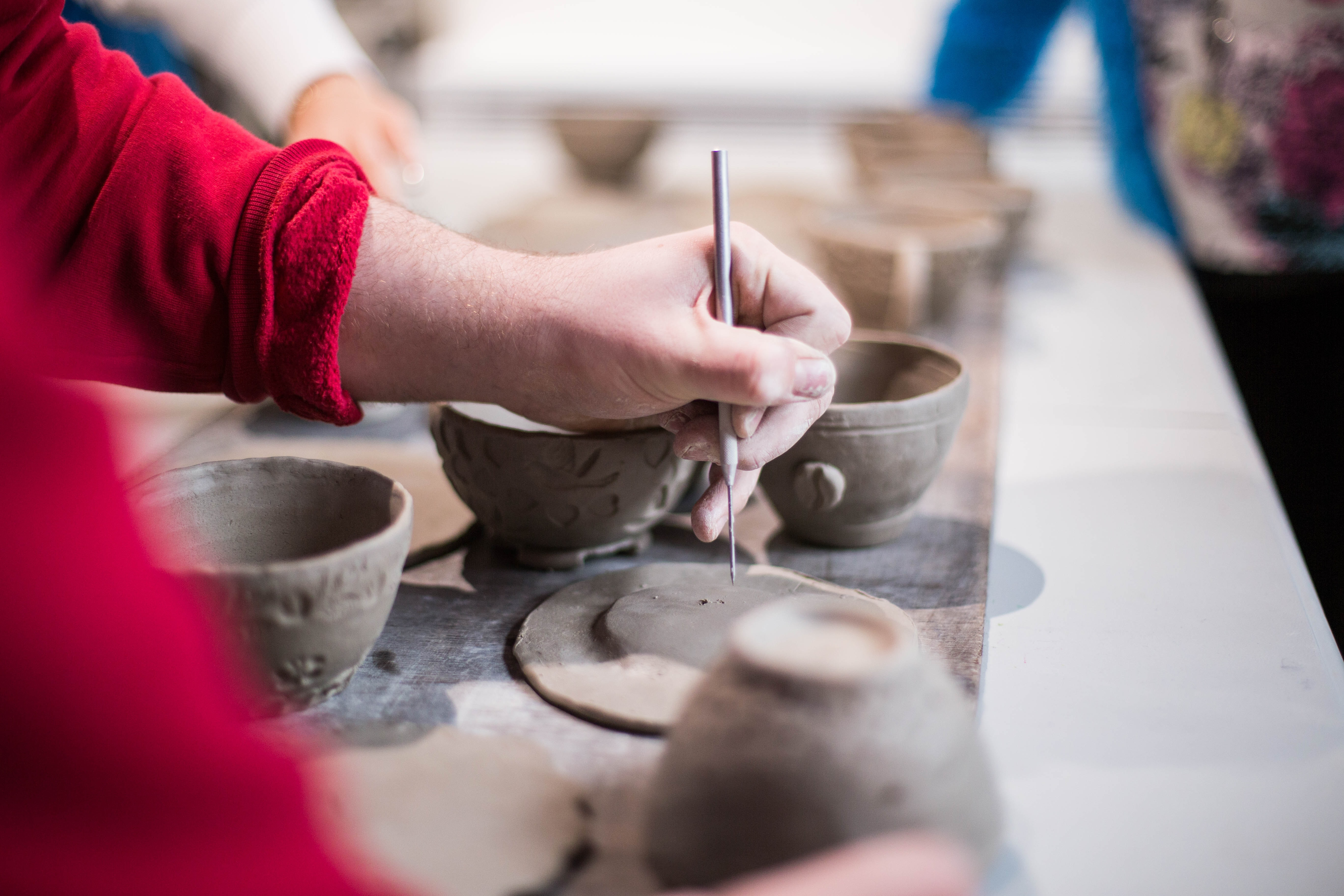 a person making indents into the clay