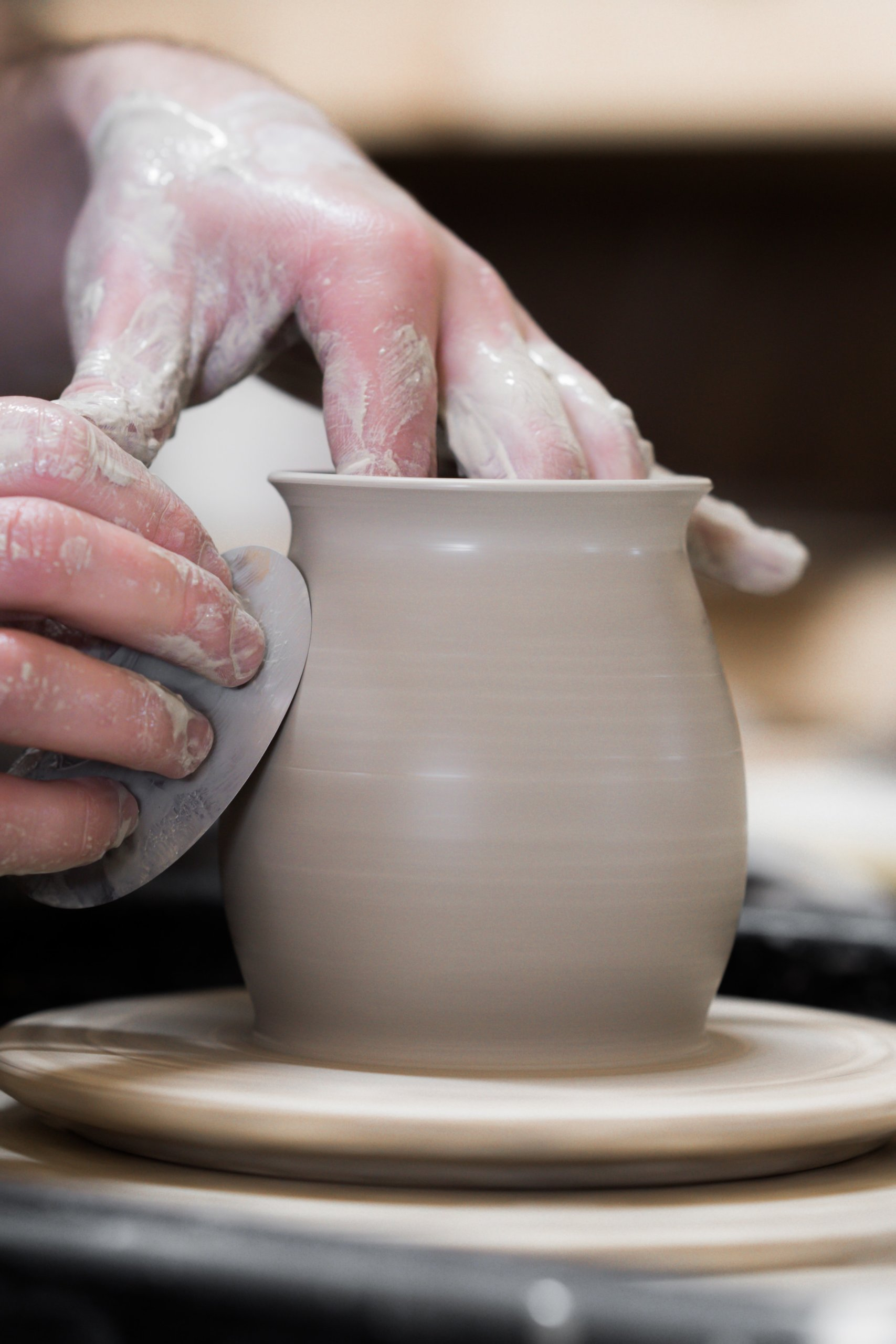 a person working clay into a pot using a potter's wheel